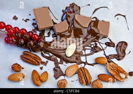 Morceaux de chocolat lisse avec sauce au chocolat et noix, et groseilles rouges Banque D'Images