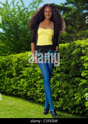 Souriante jeune femme élégante dans des vêtements colorés dans un parc