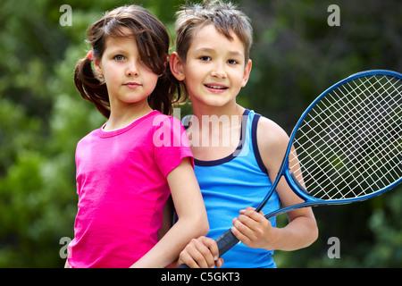 Portrait d'une petite fille et garçon avec raquette de badminton