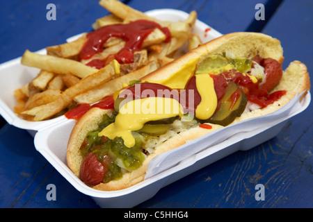 Hot-dog et frites à emporter couverts dans les sauces et condiments cornichons dans un récipient en polystyrène Banque D'Images