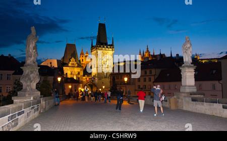 Quelques touristes sur le pont Charles au crépuscule dans Prague. Les beaux bâtiments antiques sont éclairés en lumière dorée.