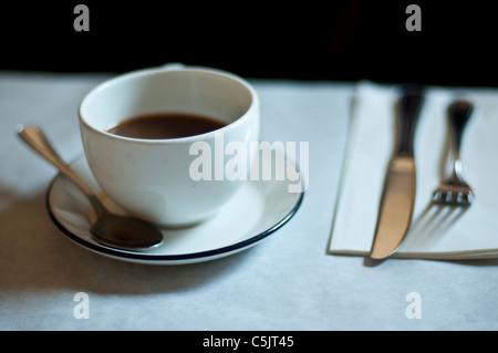 Tasse de café, cuillère, fourchette, couteau et serviette dans un petit restaurant. Banque D'Images