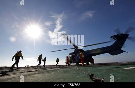 Les travailleurs du pétrole offshore sur plate-forme de forage en mer du Nord, de l'hélicoptère d'embarquement à Banque D'Images
