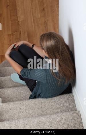 Jeune femme blonde avec des cheveux) assis tout seul dans les escaliers. Banque D'Images