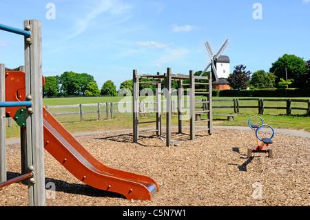 Aire de glisse et d'escalade en enclos enfants aire de jeu sur village green avec Blackmore poster mill moulin Brentwood Essex Angleterre UKUK
