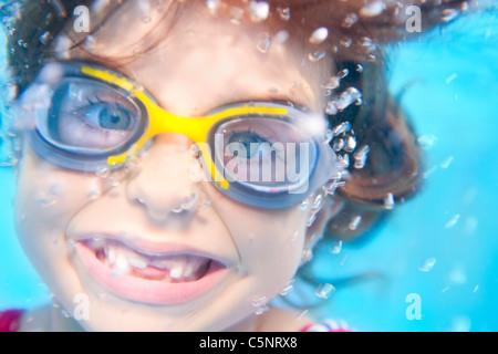 Enfants fille nager sous l'eau avec lunettes et geste drôle Banque D'Images