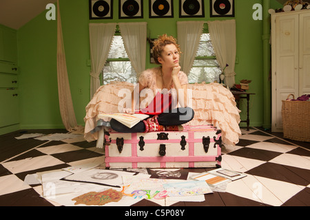 Teenage girl sitting on pouf avec des dessins sur plancher de chambre à coucher Banque D'Images