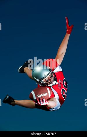 Footballeur américain volant par l'air de faire la capture. Banque D'Images