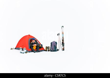 Un campeur heureux camping sur la neige. Banque D'Images