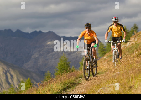 L'Italie, Livigno, View of man and woman riding mountain bike Banque D'Images