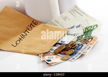 Carte d'impôt, pièces et billets en euro en paquet de salaire Banque D'Images