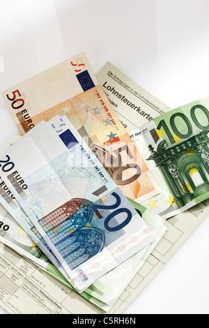 Carte d'impôt, pièces et billets en euro dans la fiche de paye, elevated view Banque D'Images