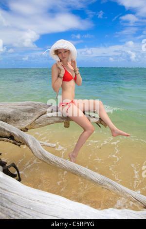 Girl in red bikini et hat est assis sur un arbre mort à l'océan Banque D'Images