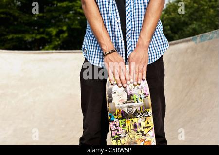 Allemagne, Düsseldorf, NRW, Man holding skateboard au skatepark publique Banque D'Images
