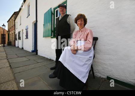 L'homme et la femme en robe victorienne s'asseoir sur le trottoir à l'extérieur de leur maison à l'Ulster Folk Park Banque D'Images