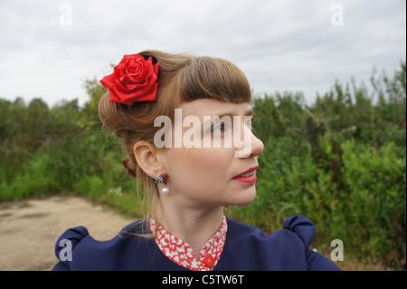 Portrait d'une femme habillée des années 40, dans un champ, rose rouge dans ses cheveux Banque D'Images