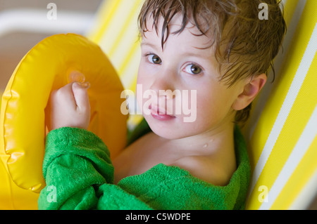 Allemagne, Baden-Württemberg, Boy (4-5) sitting on chair in indoor swimming pool, portrait Banque D'Images