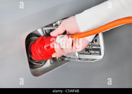 Main de femme tenant le câble haute tension de chargement de voiture électrique, Close up
