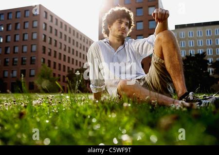 Allemagne, Berlin, Young man relaxing on Lawn, en arrière-plan les immeubles de grande hauteur Banque D'Images
