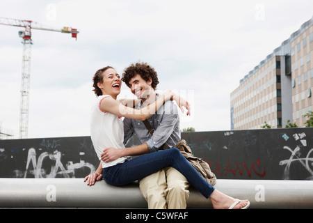 Allemagne, Berlin, Young couple in front of nouveau bâtiment, des grues en arrière-plan Banque D'Images