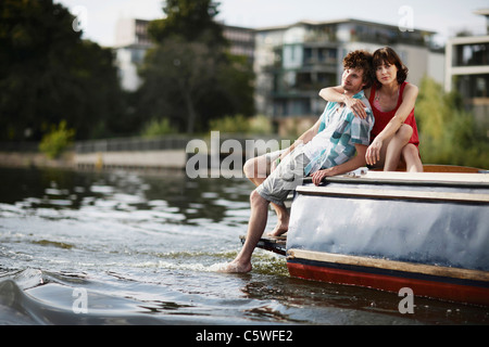 Allemagne, Berlin, Young couple sitting on motor yacht, portrait Banque D'Images
