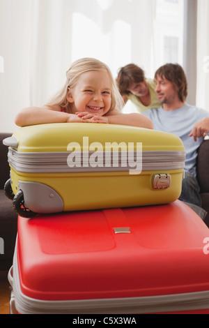 L'Allemagne, Leipzig, Girl (4-5) Valise de parents, en arrière-plan, smiling, portrait Banque D'Images