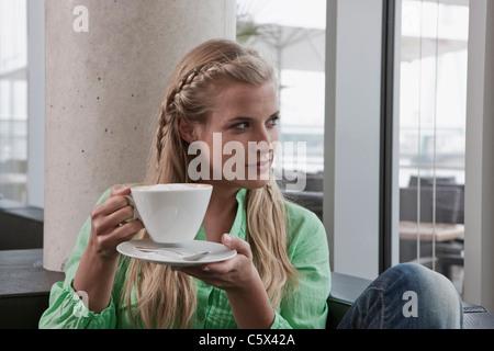 Germany, Cologne, young woman in cafe holding tasse de café, portrait Banque D'Images