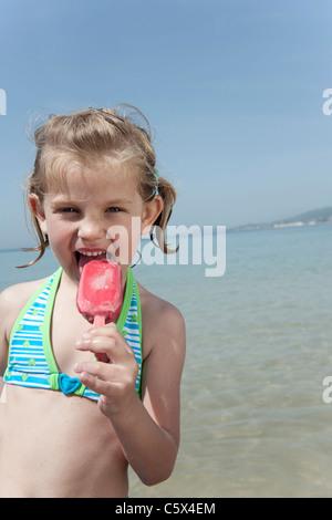 Espagne, Majorque, Girl (4-5) de manger des glaces sur la plage, portrait Banque D'Images