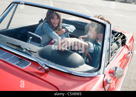 Allemagne, Berlin, Young couple sitting in cabriolet, smiling, portrait Banque D'Images
