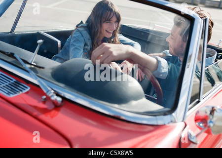 Allemagne, Berlin, Young couple sitting in convertible, rire, portrait Banque D'Images