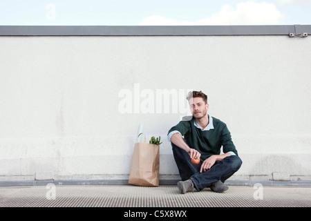 Allemagne, Berlin, jeune homme assis en face de mur, tenant une pomme, portrait Banque D'Images