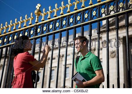 Une jeune femme de prendre une photo de son petit ami, devant le palais de Buckingham Banque D'Images