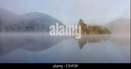 Loch an Eilein sur matin brumeux, Rothiemurchus Forest, parc national de Cairngorms, en Écosse, en Grande-Bretagne. Banque D'Images
