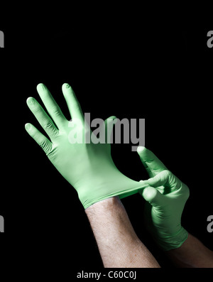 Mettre les mains sur les gants chirurgicaux Banque D'Images