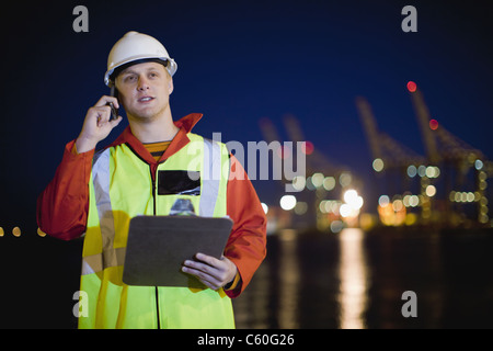 Worker talking on cell phone in shipyard Banque D'Images