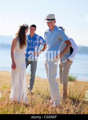 Mariée et le marié à rire avec des amis Banque D'Images