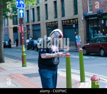 Fortement tattooed man contrôler son téléphone près du quartier chinois à Birmingham. Banque D'Images