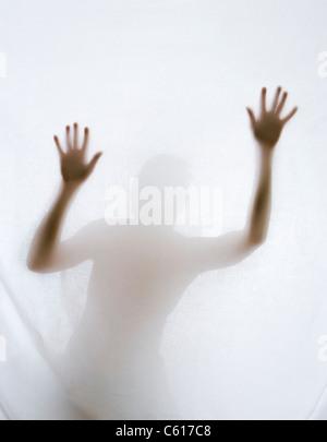 Silhouette d'homme derrière feuille. Banque D'Images