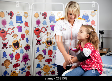 Une femme infirmière pédiatrique prend la pression artérielle d'une jeune fille à l'hôpital du patient. Banque D'Images