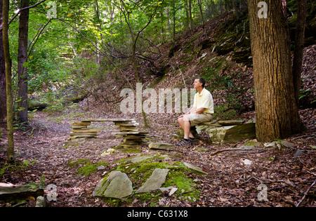 Randonneur à la retraite repose sur des bancs de pierre dans une clairière dans une forêt sur une randonnée