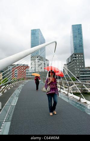 Des femmes portant un parapluie sur Santiago Calatrava Pont Zubizuri, Bilbao, dans le Pays Basque de l'Espagne Banque D'Images