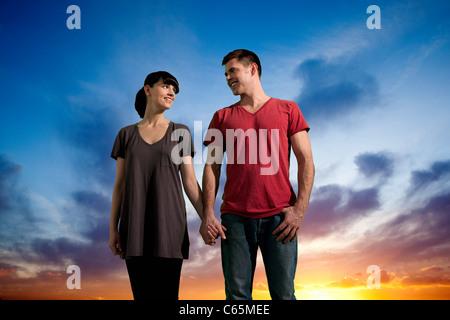 Couple holding hands against orange Banque D'Images