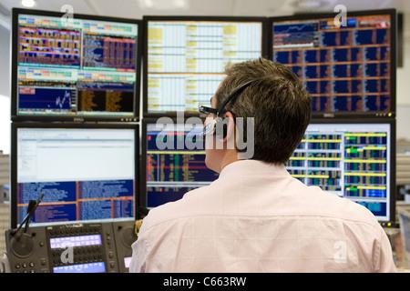 Un commerçant de porter un casque regarde son écran d'ordinateur. Banque D'Images