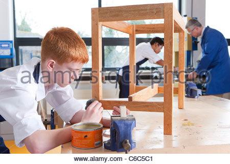 Élève de classe d'ébénisterie mettant soigneusement tache sur table en bois Banque D'Images