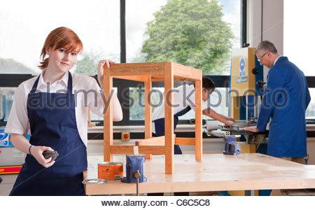 Élève de classe d'ébénisterie mettre tache sur table en bois Banque D'Images