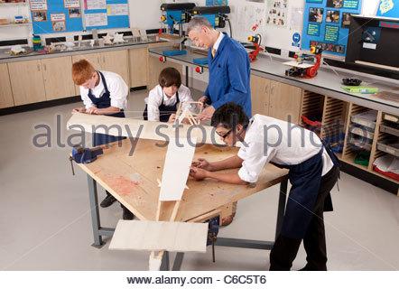 L'enseignant et les étudiants travaillant sur les grands modèles en bois avion en classe d'ébénisterie Banque D'Images