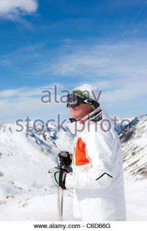 Smiling homme portant des lunettes de ski et la tenue des bâtons de ski sur la montagne enneigée Banque D'Images
