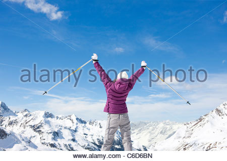 Bâtons de ski woman with arms outstretched on snowy mountain top Banque D'Images