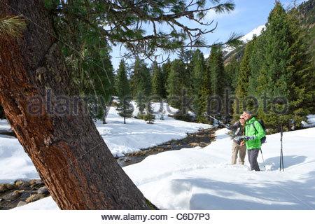 Couple avec des bâtons de ski et la carte pointant dans Snowy Woods Banque D'Images