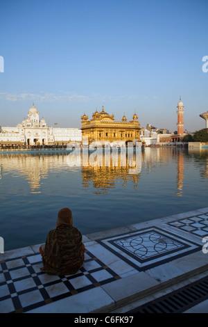 Un dévot est assis à l'entrée du petit lac qui entoure le 16e siècle, le Temple d'or sikh à Amritsar, Inde, l'État Banque D'Images
